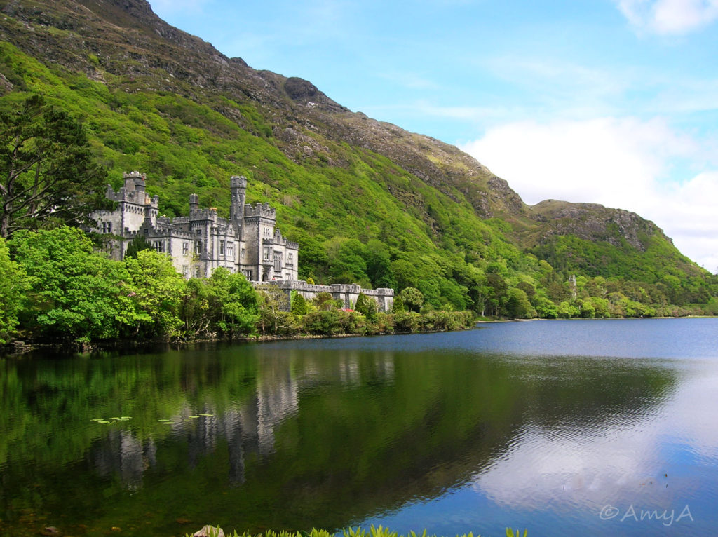 Kylemore Abbey, Ireland. A huge gothic-looking caste-like structure on the water.