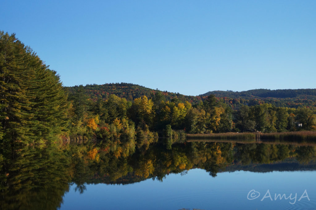 "Vermont in October. This is what I call an ""accident"" shot. I was sitting in the passenger seat as we were driving past and I was like (in my head), ""I must have this picture! Look at the colours! Look at the reflection on the water!"" So I pointed and shot without bothering to adjust my camera settings (we were going too fast and I would've missed it had I paused for even just another second), and here you have the result. Not bad considering we were going at least 80km/h. If you look closely to the tree on the left, it's slightly blurry."